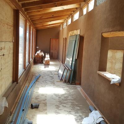 Galeria colonial, paredes de barro, ventanas de roble.