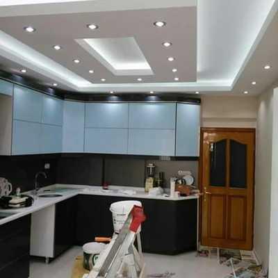 Cocina con techo falso con iluminación indirecta acompañado con bombillos LED.