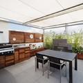 Comedor y cocina bajo pérgola de aluminio