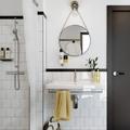 espejo redondo en baño blanco