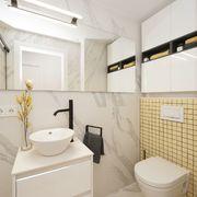 Baño en blanco y amarillo con azulejo de mármol
