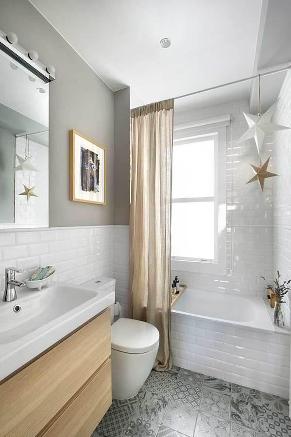 baño con bañera y azulejos a media altura