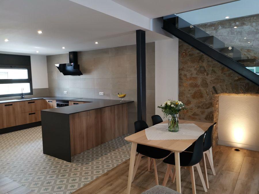 Comedor y cocina con escalera de cristal