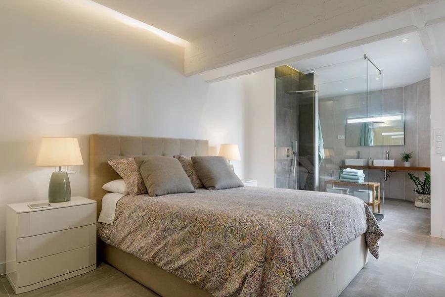Dormitorio con baño integrado mediante paredes de pavés o vidrio