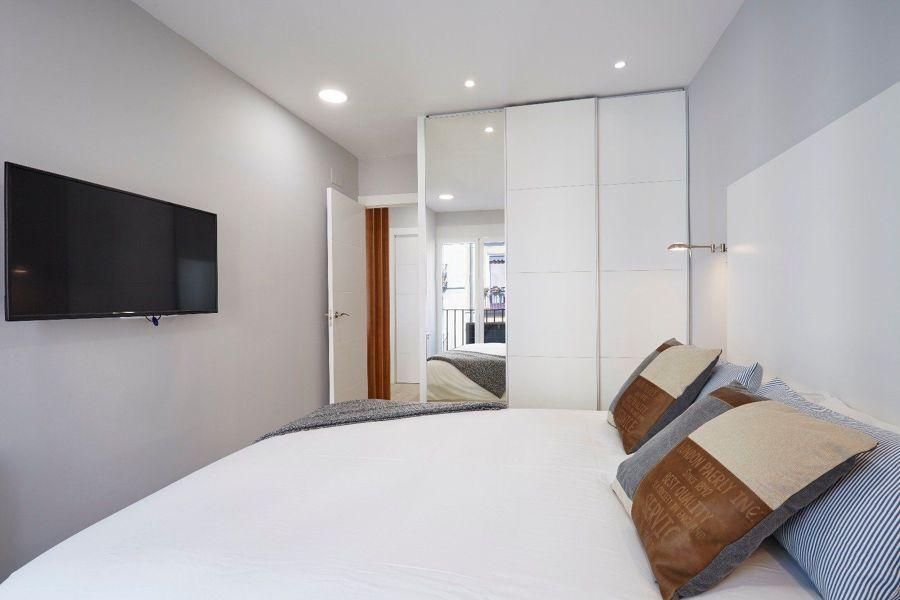 Dormitorio con pared armario empotrado con puertas de espejo