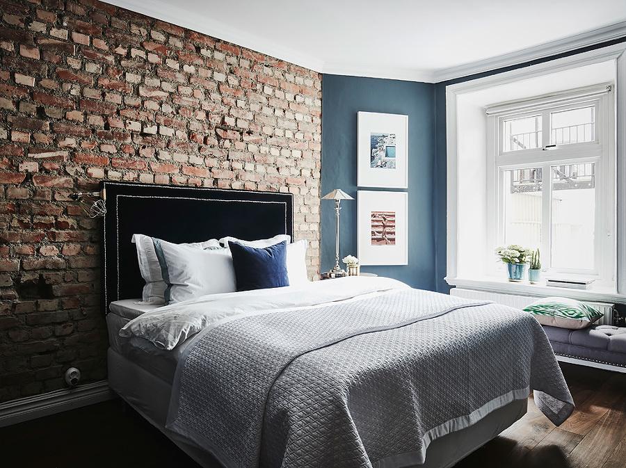Dormitorio con pared ladrillo visto