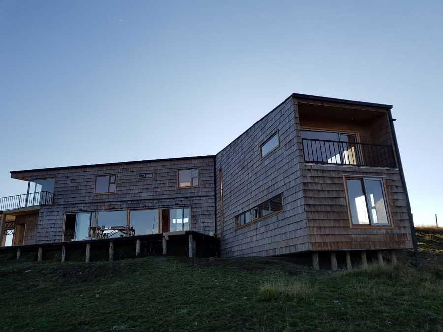 fachada exterior con tejuela de alerce y terminaciones de mañío