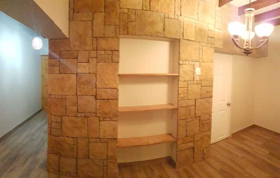 Revestimiento de piedra en muro y repisas en madera de Radal