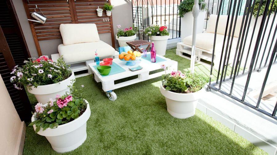terraza con mesa de pallets y pasto artificial